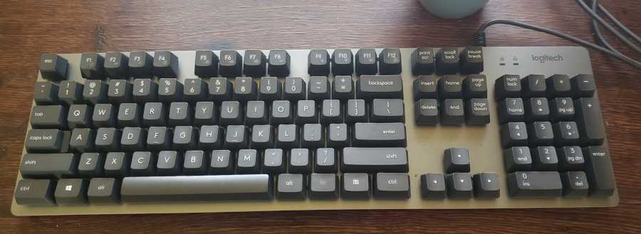 logitech k840 mechanical keyboard sitting on old oak wood desk