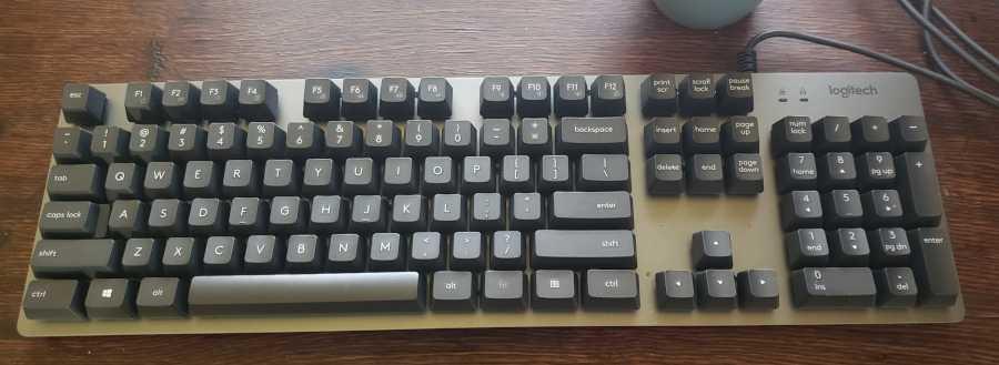 logitech k840 mechanical keyboard sitting on old oak wood desk